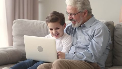 Happy old grandfather and little cute grandson laughing looking at laptop sitting on sofa, grandkid small boy sit on senior grandpa lap talking teaching using laptop having fun with computer at home