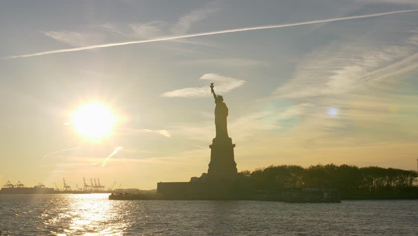 Statue Of Liberty In New York City From The Hudson Manhattan Ferry, USA. Hudson River. Establishing Shot. Famous Statue In NYC.Tourist Attraction. Golden Hour. Sun Beaming Through.