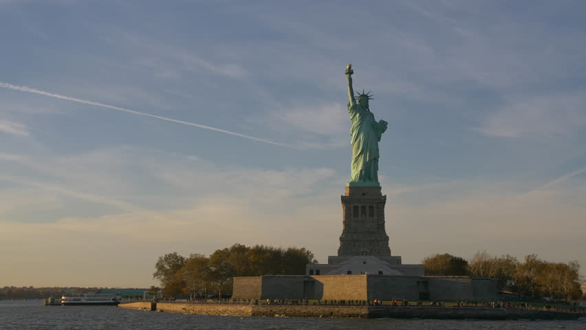 Statue Of Liberty In New York City From The Hudson Manhattan Ferry, USA. Hudson River. Establishing Shot. Famous Statue In NYC. Tourist Attraction. Beautiful Blue Sky.