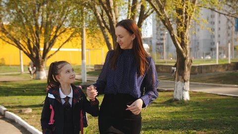 Mother is walking little girl in a school uniform to school. Mother and daughter together holding hands going to school.