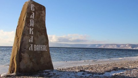 Shore of lake Baikal. On the big stone is written in Russian - Baikal. Snow-covered mountains in the background. Static frame