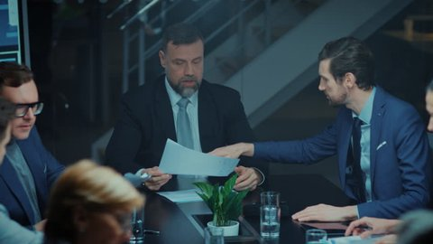Corporate Meeting Room: Sitting at the Conference Table Charismatic Director Talks Enthusiastically and Gesticulates Energetically proving His point to Investors, Lawyers, Executives