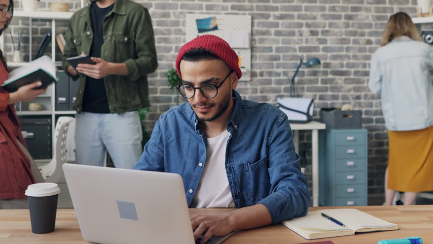 Zoom out time-lapse of male employee handsome hipster in trendy clothing working with laptop busy with project in office. Coworkers are moving around. | Shutterstock HD Video #1028623136