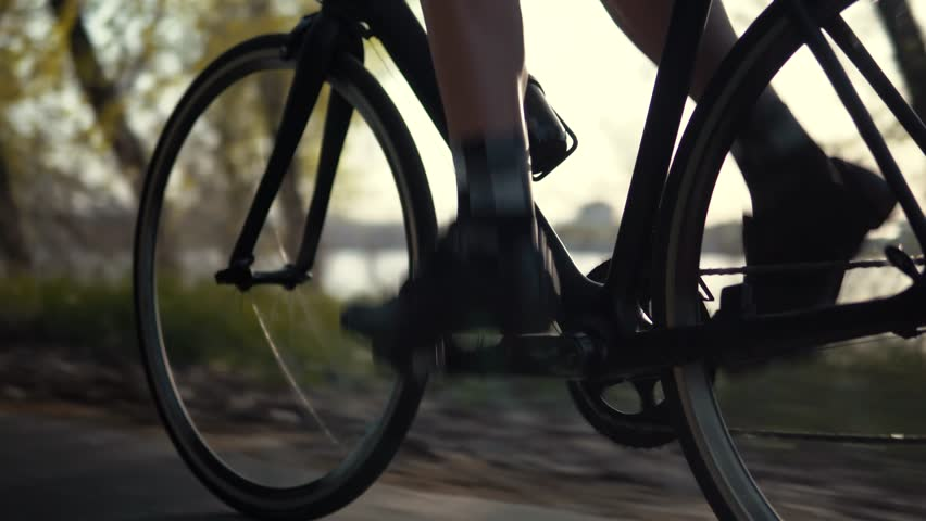 Close Up Twists Pedals Of A Bicycle.Cycling At Sunset On City Park.Gear System Road Bicycle.Close Up Bicycle Wheel Rotation.Close Up Cyclist Riding On A Road Bicycle.Close-Up Cyclist Pedaling On Velo	 | Shutterstock HD Video #1028623436