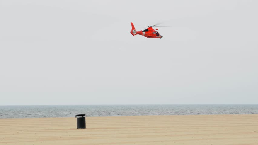 This video shows a red coast guard helicopter flying away on a cloudy beach.