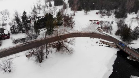 Aerial, drone shot, of a car driving on a slushy road, near Blakeney rapids, at snowfall, on a winter day, in Mississippi Mills, Ontario, Canada