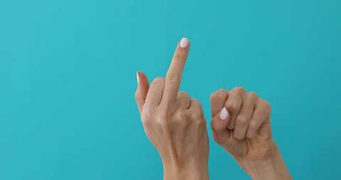 Woman hand gesture meaning in western cultures Fuck you or fuck off isolated blue screen