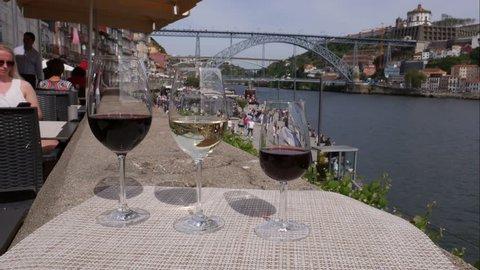 Porto, Portugal - April 29, 2019: Time lapse of Red, white and Porto wine glasses overlooking tourists at Cais da Ribeira and Ponte de Dom Luis I on the River Douro in Porto, Portugal - 4K
