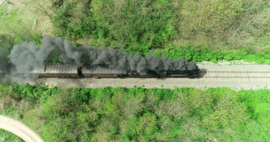Historic train with steam locomotive and old carriages runs on the tracks in the countryside. Aerial view.
