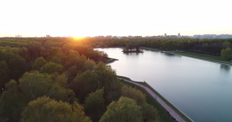 Aerial view of the park and lake at sunset. Drone video of park and lake complex and manor house Kuskovo at sunset time. Moscow, Russia. | Shutterstock HD Video #1028693336