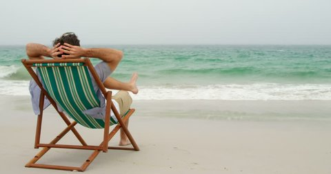 Rear view of man relaxing with hands behind head on sun lounger at beach. He is looking at sea.