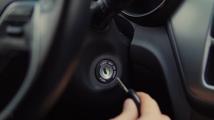Close-up shot of a man putting his car keys into socket and starting the engine. Man's hand with car keys. Igniting car. | Shutterstock HD Video #1028733206