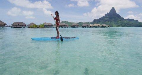 Stingray and Adventure travel woman on SUP Paddleboard by stingrays at Bora Bora luxury resort hotel on travel vacation in Tahiti, French Polynesia. Asian bikini girl having fun watersport activty.