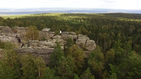 Aerial view of drone with typical Portuguese forest, crown of trees, pines and oaks, beauty of nature. Footage. Two men travelling in spectacular valley with granite mountains and beautiful forest.