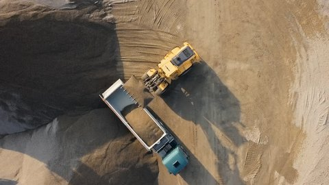 Top aerial view of bulldozer loading stones into empty dump truck in open air quarry.