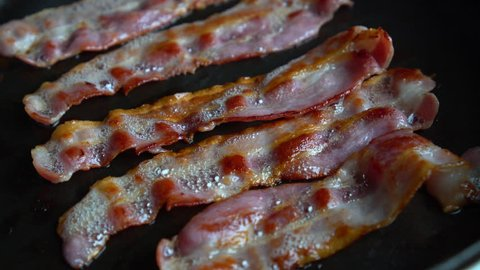 Crispy and thin bacon, rich in fat and colour, sizzling and smoking in a hot pan.