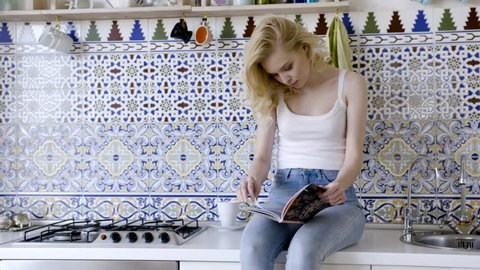 Woman reading magazine at kitchen table. Action. Young blonde woman reading a magazine in the kitchen