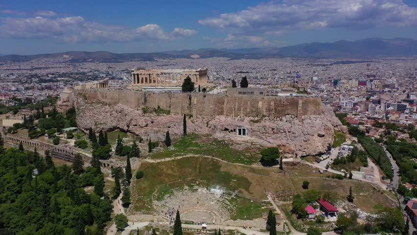 Aerial drone bird's eye view video of iconic Acropolis hill, the Parthenon and famous theater of Dionysus with beautiful sky and clouds, Athens historic centre, Attica, Greece #1028848316
