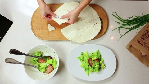 Top down view of the female cook breaking round thin pita bread into small pieces on wooden board. Preparing dinner, freshly-cooked salad on the table