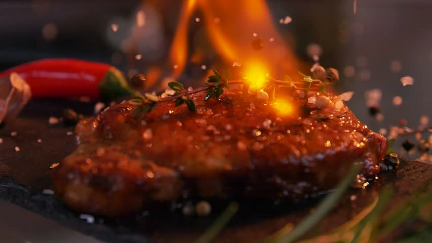 Slow-motion footage of throwing salt and pepper on fresh beef meat on ignited pan. | Shutterstock HD Video #1028888006