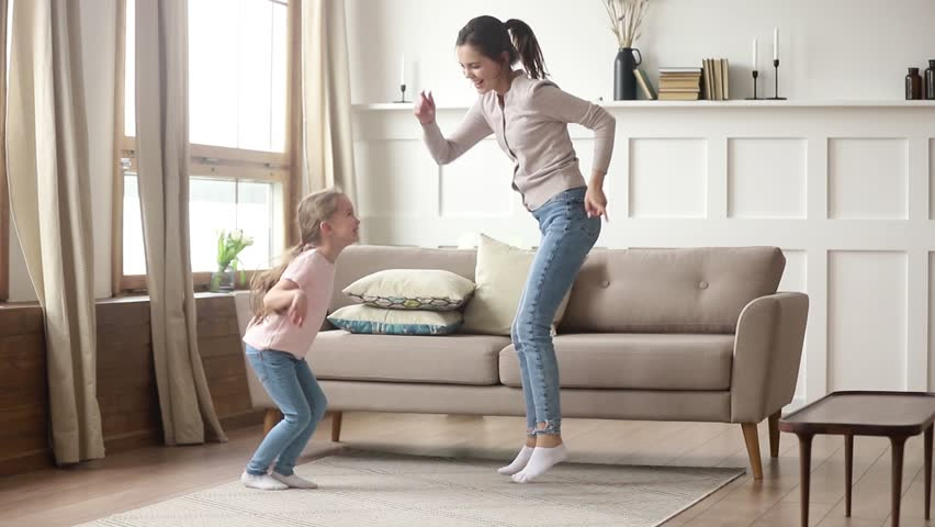 Happy family young mom babysitter having fun with cute little kid girl dancing in living room, carefree mother with child daughter laughing jumping enjoying funny activity playing together at home