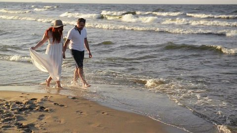 Young Couple In Love On The Beach. Beautiful Couple In White Clothes. Lovers Holding Hands And Hugging.