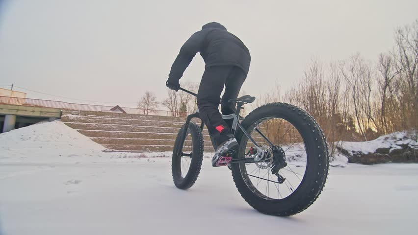 Professional extreme sportsman biker riding fat bike in outdoors. Close-up view of rear wheel. Cyclist ride in winter forest. Man on mountain bicycle with big tire. Snow fly into the lens camera. | Shutterstock HD Video #1028927186