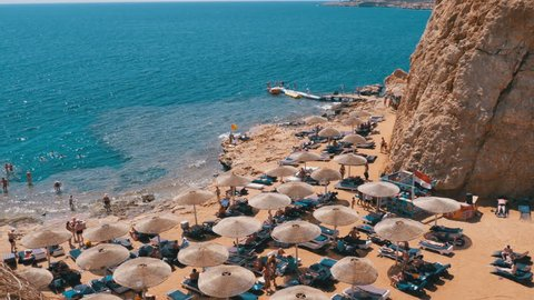 Egypt, Beach with Umbrellas and Sunbeds on Red Sea near the Coral Reef. Resort on Red Sea Coast. Rocky Beach in a Bay. The coastline with coral reefs and waves. Panoramic view of the Sharm El Sheikh