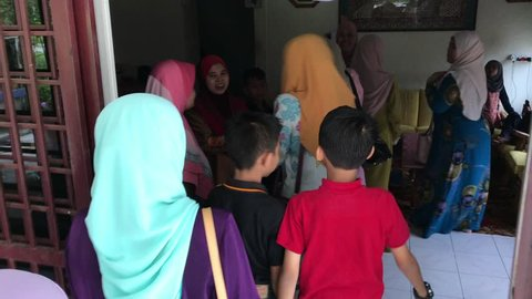 Kota Bharu, Malaysia -June 17th, 2018 : Muslim family back home and hugging shake hand while visiting their relatives during Eid al-Fitr celebration .Family, Happiness and Forgiveness Concept.