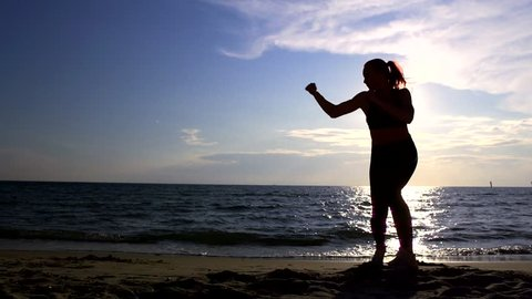 Young female athlete practicing Boxing martial arts on the beach above the sea at the amazing sunrise. Fitness, sports, kickboxing and healthy lifestyle concept. slow motion