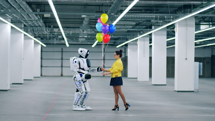 Young lady is giving colourful balloons to a robot | Shutterstock HD Video #1028988536