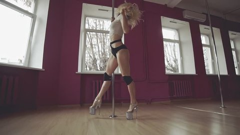 Wide view of young beautiful woman performs sensual dance in slow motion. Pole Dance. Beautiful woman doing poledance in studio. Exotic dance. Young slim girl dancing near pole