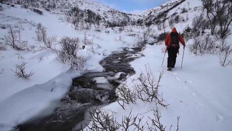 Stream Crossing During Winter Trek in Lofoten, Norway