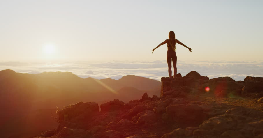 Beautiful young woman performing a spiritual yoga pose on the top of a mountain at sunrise in slow motion, sunrise zen wellness
