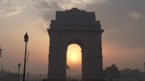 A zoom in shot of the sun and india gate at sunrise in new delhi, india