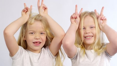 Chest-up shot of cheeky 5-year-old Caucasian twin sisters posing with playful bull horns hand gestures in studio on white background, talking and looking at camera with gap-toothed smiles