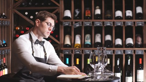 Portrait of sommelier perfectly skilled in wine etiquette, selecting wines, exquisite service for presenting wine to the customer putting down some notes in his note pad in restaurant.