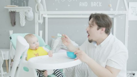 Caring young dad clumsily feeding cute infant daughter with puree in nursery. Toddler girl with stained face and clothes eating from spoon willingly opening mouth sitting on high children's chair.