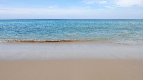 Small, gentle waves wash onto the smooth sand of a peaceful beach. Low angle view of a turquoise sea and waves lapping at the shore. Blue sky and soft white clouds on the horizon. Wide, empty scene.