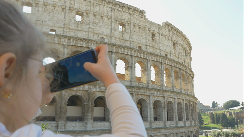 Cute little girl with parents takes photos of city sights, family trip to Rome