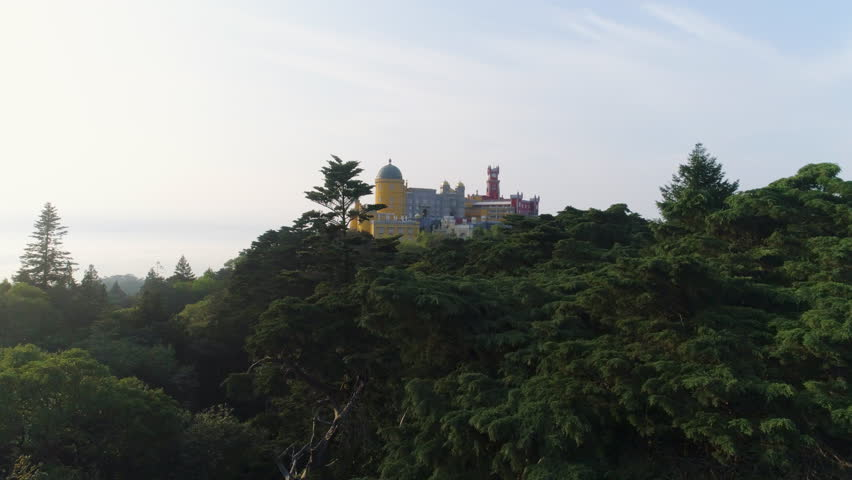 Aerial view forest park in mountains at sunset time. Drone rising above treetops and flying forward to palace Pena on peak over Sintra town in bottom. | Shutterstock HD Video #1029273746