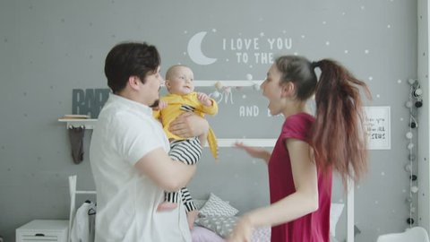 Close-up of happy family with baby daughter enjoying domestic leisure and dance. Cheerful father holding toddler girl and making dancing movements together with little child and joyful young wife.