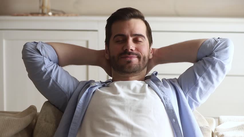 Calm happy young man relaxing with eyes closed on comfortable couch holding hands behind head breathing fresh air, lazy serene millennial guy chilling on sofa enjoy stress free peaceful day at home | Shutterstock HD Video #1029331796