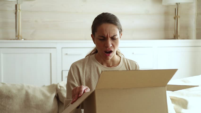 Dissatisfied annoyed female customer open cardboard box receive damaged broken parcel, shocked young woman consumer having problem complaint frustrated with bad shopping order delivery post shipping
