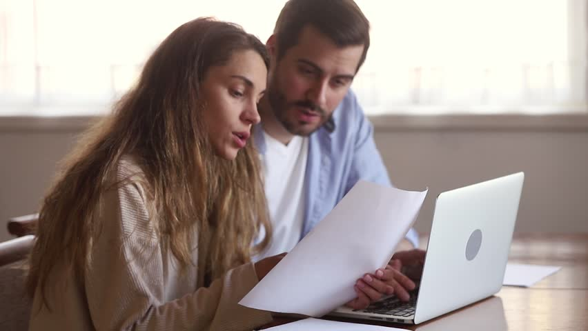 Serious young couple holding papers pay domestic bills online on laptop checking bank account reading document at home, millennial family planning budget discussing money finances expenses