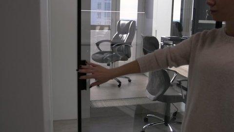 Girl's hand open the door with glass reflection background.Girl's hand open the door with glass reflection background. Businessman Entering an Office