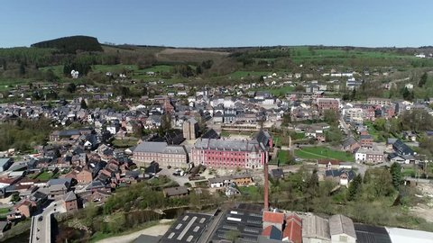 Aerial bird view footage flight towards Abbey of Stavelot located in the Walloon municipality in Belgian province of Liege at Ardennes region popular tourist destination know by beautiful nature 4k