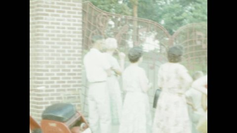 1950s: People stand outside the gates at Graceland. Gates open, small car drives through, women get out of car.