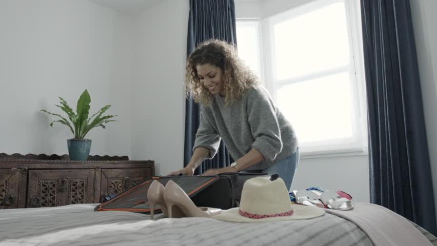 Smiling woman packing her holiday clothes into a suitcase ready for summer vacation fun | Shutterstock HD Video #1029410186