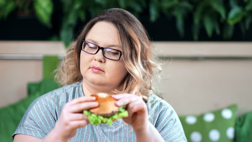 Portrait of doubtful fat woman on diet refusing from unhealthy burger fast food